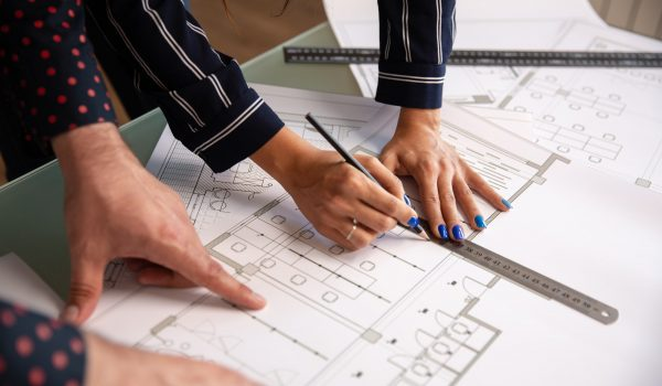 Close up with the hands of two architects who draw something in a house plan